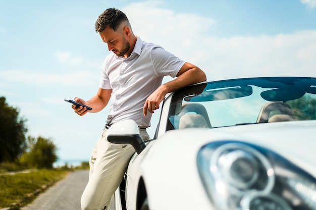 Homme regardant téléphone coup moyen Photo gratuit
