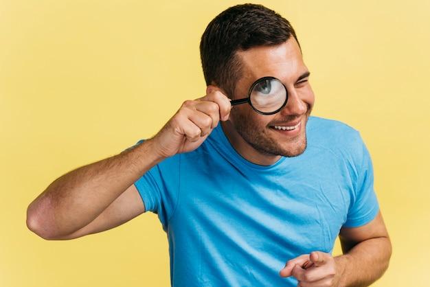 Homme regardant à travers une loupe Photo gratuit