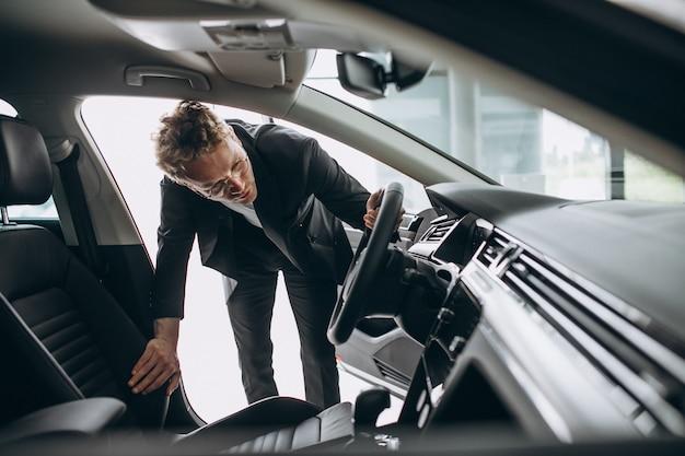 Homme regardant une voiture dans une salle d'exposition Photo gratuit