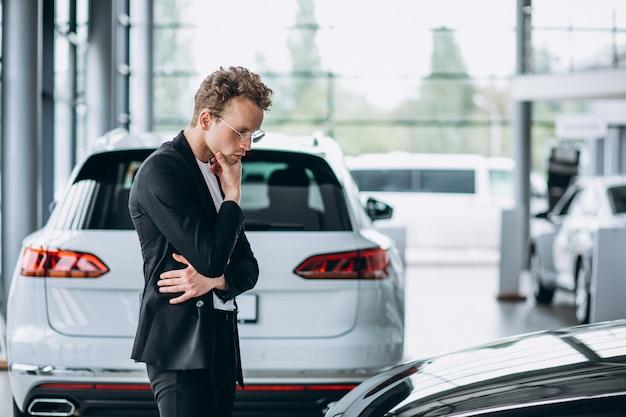 Homme regardant une voiture et songeant à un achat Photo gratuit