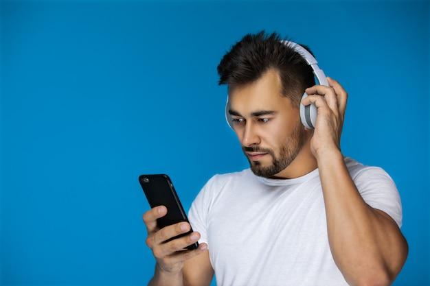 L'homme Regarde Quelque Chose Au Téléphone Et écoute Avec Les écouteurs Photo gratuit