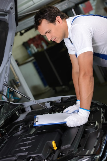 L'homme regarde sous le capot de la voiture et cherche une casse. Photo Premium