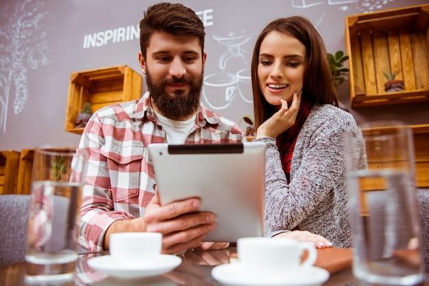 Un homme regarde une tablette dans un café. Photo Premium