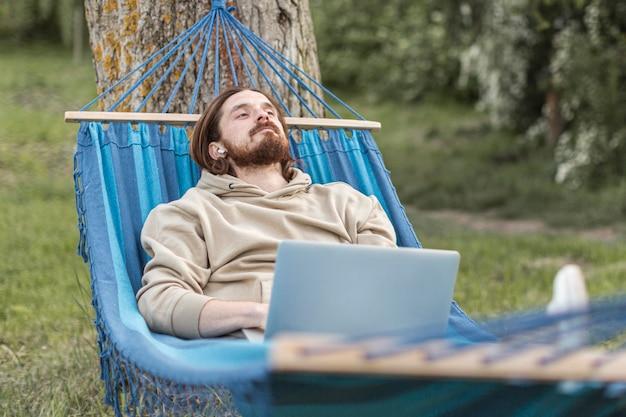 Homme Relaxant Dans La Nature Tout En étant Assis Dans Un Hamac Photo gratuit