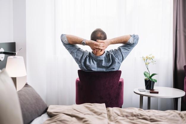 Homme relaxant, posant dans fauteuil Photo gratuit