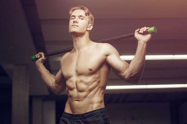 Homme De Remise En Forme à L'entraînement Dans Une Salle De Sport Avec Des Muscles D'étirement Bodybar Photo Premium