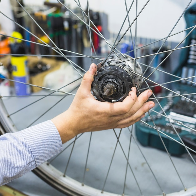 Homme réparant un pneu de vélo en atelier Photo gratuit
