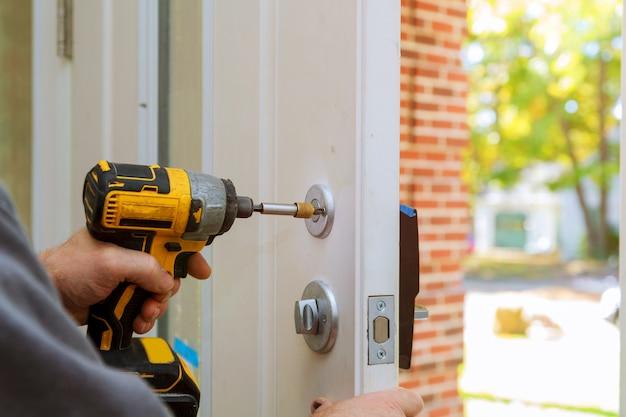 Homme réparant la poignée de porte. gros plan des mains du travailleur installant un nouveau casier de porte Photo Premium