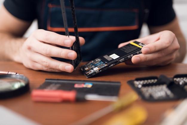 Un homme répare un téléphone portable au travail Photo Premium
