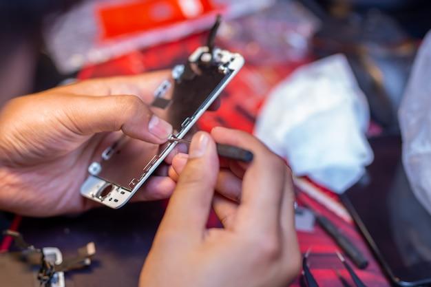 Un homme répare un téléphone portable Photo Premium