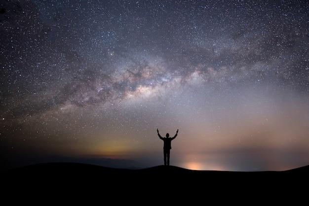 Homme réussi silhouette au sommet de la colline sur un fond d'étoiles Photo gratuit