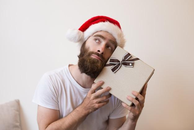 Homme rêveur essayant de deviner ce qu'il y a à l'intérieur d'une boîte cadeau de noël Photo gratuit