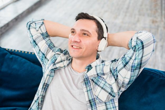 Homme rêveur souriant écoute de la musique au casque sur le canapé Photo gratuit