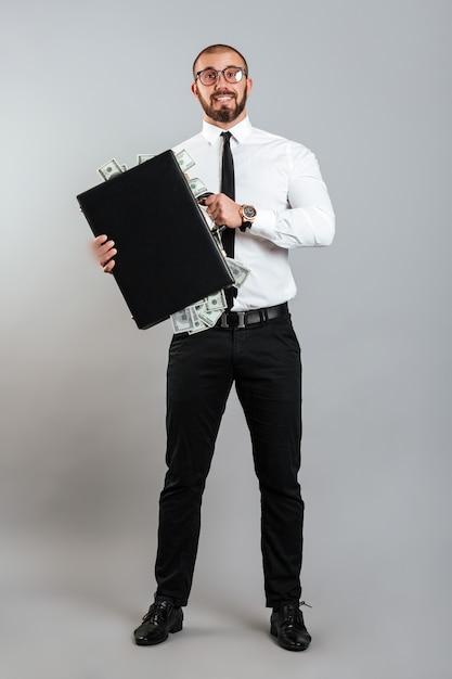 Homme Riche Entrepreneur Dans Des Verres Et Costume D'affaires Tenant Diplomate Plein D'argent Dollar, Isolé Sur Mur Gris Photo Premium