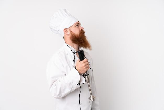 Homme Rousse à L'aide D'un Mélangeur à Main Sur Un Mur Blanc Isolé à La Recherche De Côté Photo Premium