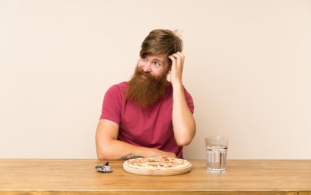 Homme rousse avec une longue barbe dans une table et avec une pizza ayant des doutes et avec une expression du visage confuse Photo Premium