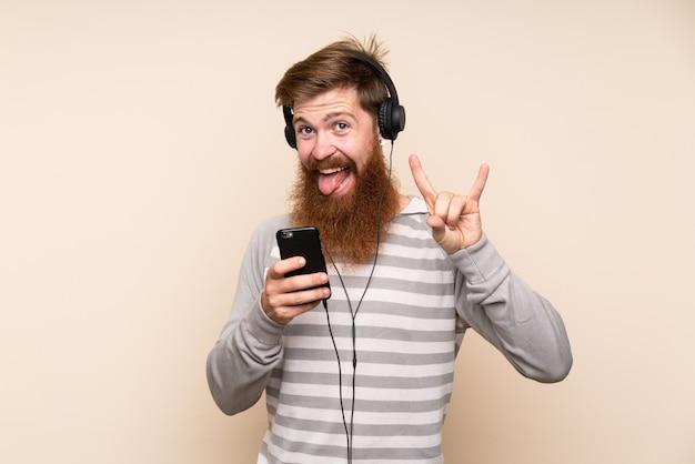 Homme Rousse Avec Une Longue Barbe Sur Fond Isolé à L'aide Du Mobile Avec Des écouteurs Et Chantant Photo Premium