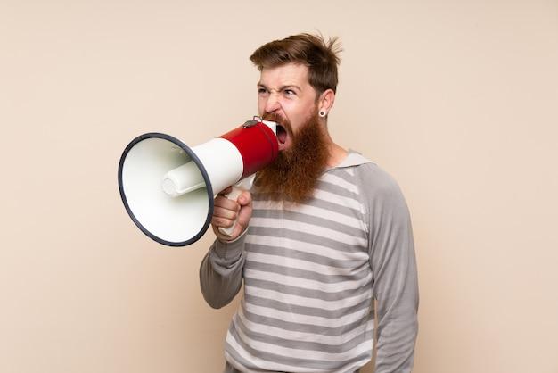 Homme rousse avec une longue barbe sur fond isolé en criant à travers un mégaphone Photo Premium