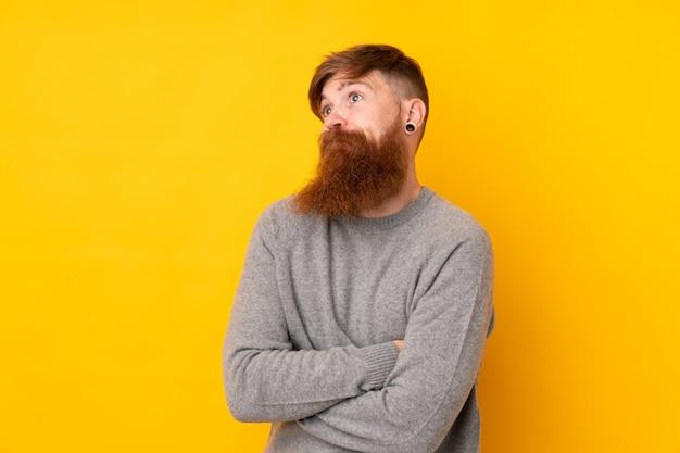 Homme Rousse Avec Une Longue Barbe Sur Un Mur Jaune Isolé Faisant Un Geste De Doute Tout En Soulevant Les épaules Photo Premium