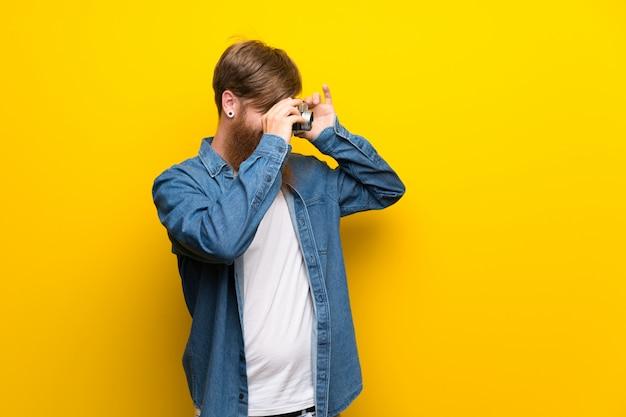 Homme rousse avec une longue barbe sur un mur jaune isolé, tenant une caméra Photo Premium