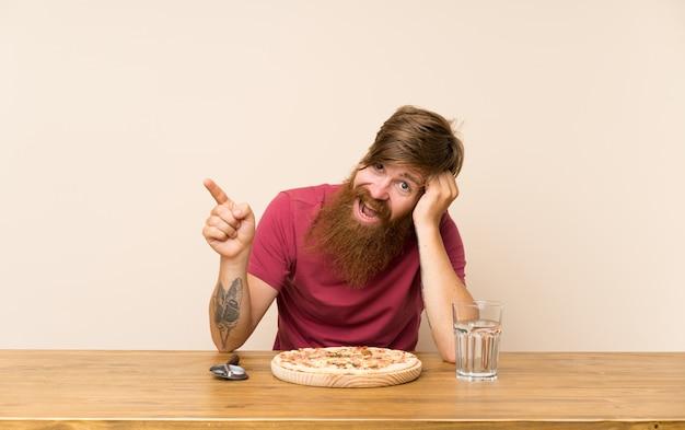 Homme rousse avec une longue barbe sur une table et une pizza surprise et pointant du doigt sur le côté Photo Premium