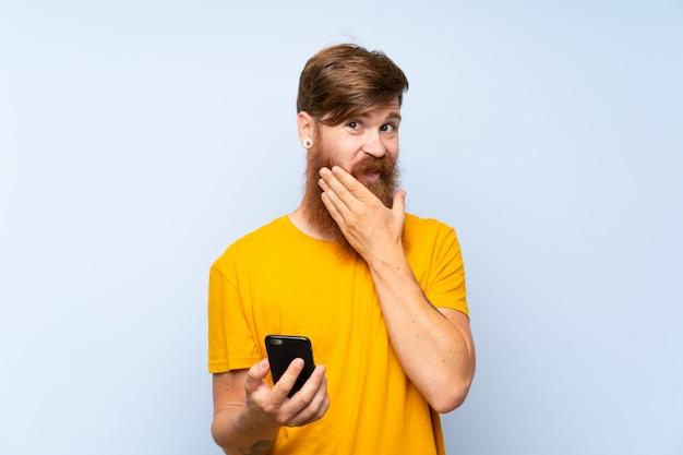 Homme Rousse Avec Une Longue Barbe Avec Un Téléphone Portable Sur Un Mur Bleu, Pensant à Une Idée Photo Premium