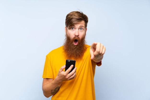 Homme rousse avec une longue barbe avec un téléphone portable sur le mur bleu surpris et pointant le devant Photo Premium