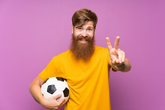 Homme rousse avec une longue barbe tenant un ballon de football sur un mur violet isolé, souriant et montrant le signe de la victoire Photo Premium