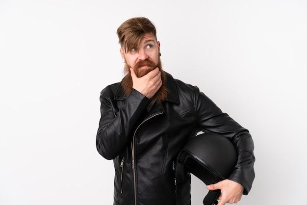 Homme Rousse à Longue Barbe Tenant Un Casque De Moto Sur Un Mur Blanc Isolé En Pensant à Une Idée Photo Premium