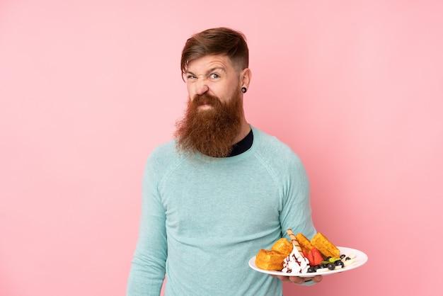 Homme Rousse Avec Une Longue Barbe Tenant Des Gaufres Sur Un Mur Rose Isolé Faisant Un Geste De Doute Tout En Soulevant Les épaules Photo Premium
