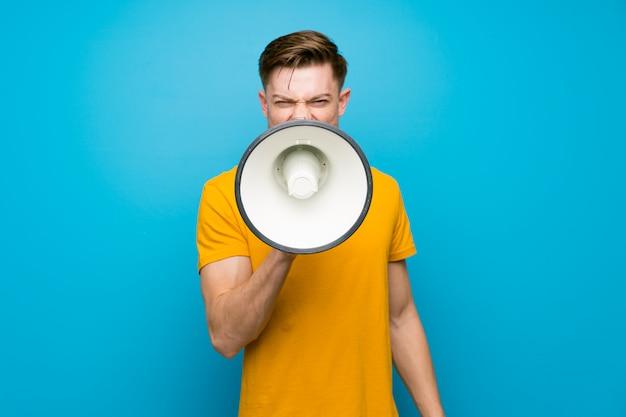 Homme rousse sur un mur bleu criant dans un mégaphone Photo Premium