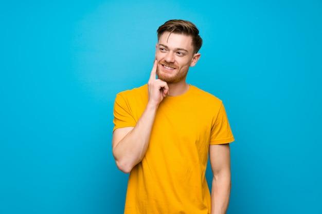 Homme rousse sur le mur bleu pense à une idée tout en levant les yeux Photo Premium
