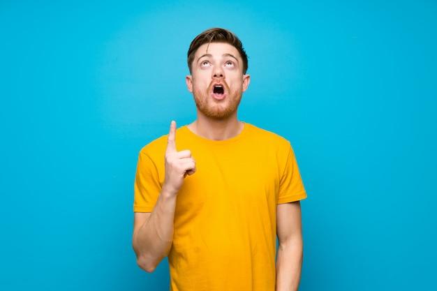 Homme rousse sur un mur bleu pointant vers le haut et surpris Photo Premium