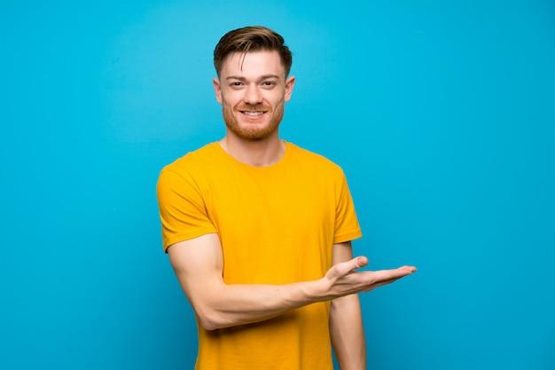 Homme rousse sur un mur bleu présentant une idée tout en regardant en souriant Photo Premium