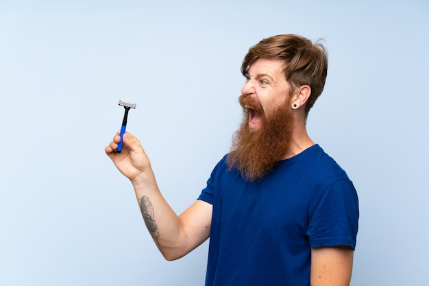 Homme rousse rasant sa barbe sur un mur bleu isolé Photo Premium