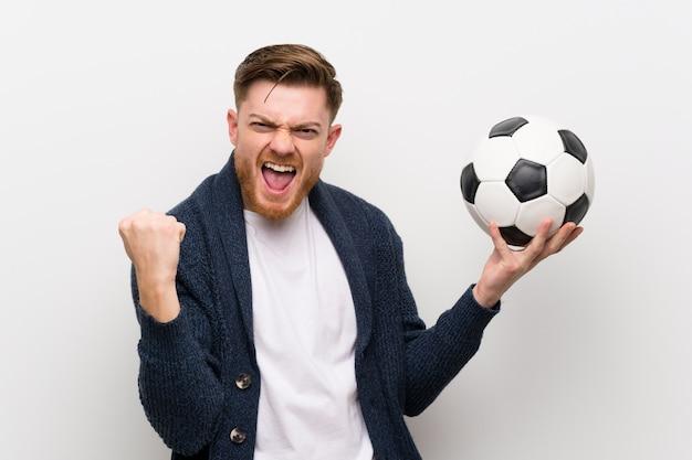 Homme rousse tenant un ballon de foot Photo Premium