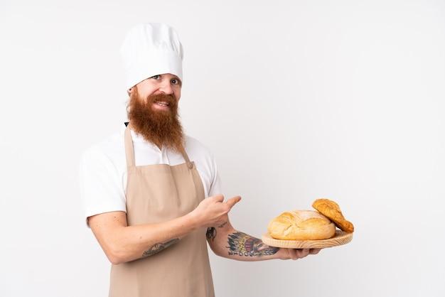 Homme Rousse En Uniforme De Chef. Boulanger Mâle Tenant Une Table Avec Plusieurs Pains Et En Le Pointant Photo Premium
