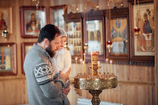 Un homme russe avec une barbe et une fille est debout dans une église orthodoxe Photo Premium