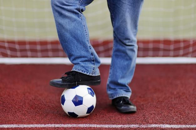 Homme s'amusant à jouer à un match de foot / football le jour d'été Photo Premium