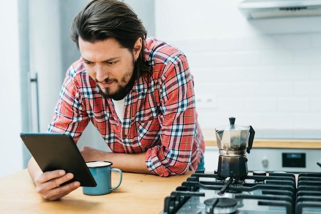 Un homme s'appuyant sur le comptoir de la cuisine en regardant un téléphone intelligent Photo gratuit