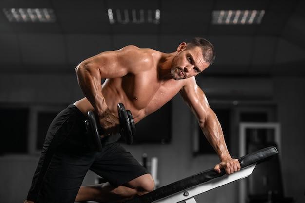 Homme s'entraîne dans le gymnase homme athlétique s'entraîne avec des haltères, pompant son biceps Photo Premium