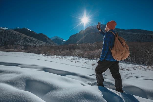 Homme avec sac à dos, trekking en montagne. temps froid, neige sur les collines. randonnée d'hiver. soleil et neige Photo Premium