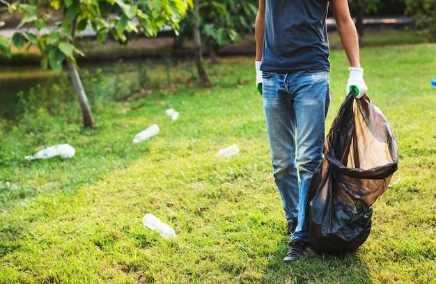 Homme avec un sac en plastique ramasser des bouteilles dans le parc Photo Premium