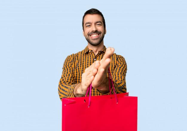 Homme avec des sacs à provisions applaudissant après présentation lors d'une conférence sur fond bleu isolé Photo Premium