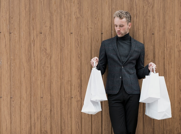 Homme avec des sacs à provisions sur fond en bois Photo gratuit
