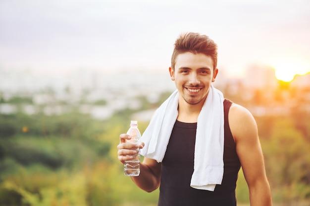 Homme Sain, Boire De L'eau Sur La Nature Au Repos Photo gratuit