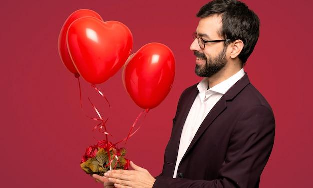 Homme à la saint-valentin applaudissant après la présentation lors d'une conférence sur fond rouge Photo Premium