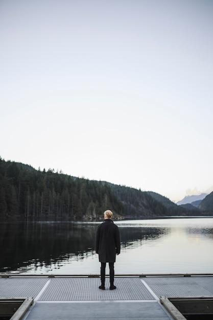 Homme sans visage en regardant l'eau Photo gratuit