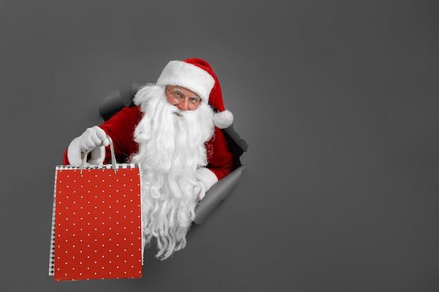 L'homme De Santa Tient Le Paquet De Magasins Dans La Main à Travers Un Trou De Papier. Homme Barbu En Bonnet De Noel Regardant à Travers Le Trou Sur Papier Gris. Photo Premium