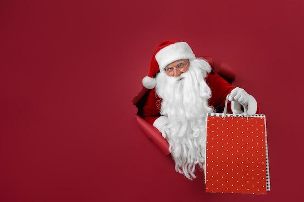 L'homme De Santa Tient Le Paquet De Magasins Dans La Main à Travers Un Trou De Papier. Homme Barbu En Bonnet De Noel Regardant à Travers Le Trou Sur Papier Rouge. Photo Premium